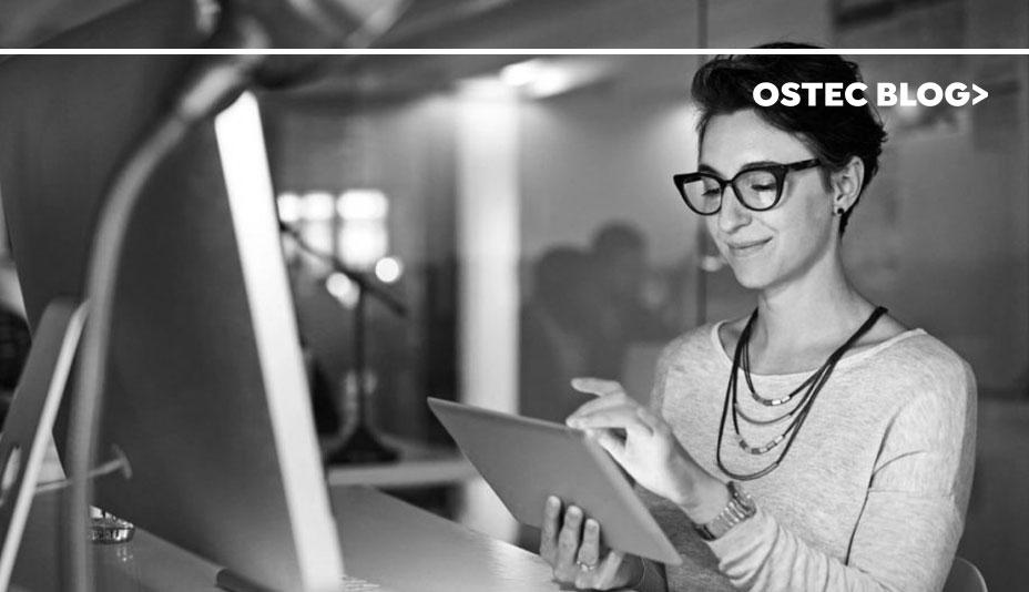Mulher utilizando internet em tablet com uma tela de computador em sua frente