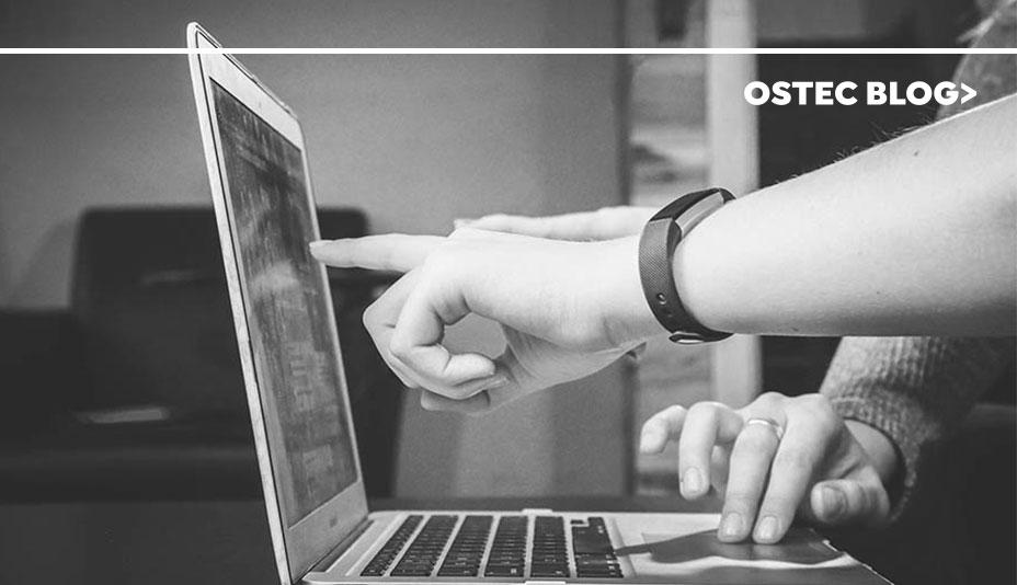 Duas mãos apontando para tela de notebook.