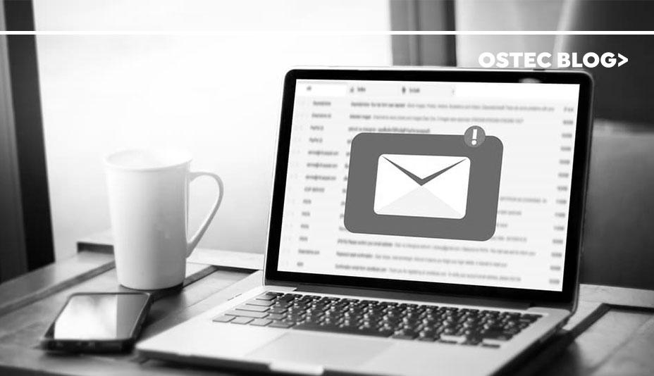 Notebook aberto sobre uma mesa com ícone de e-mail contendo notificação centralizado em sua tela.