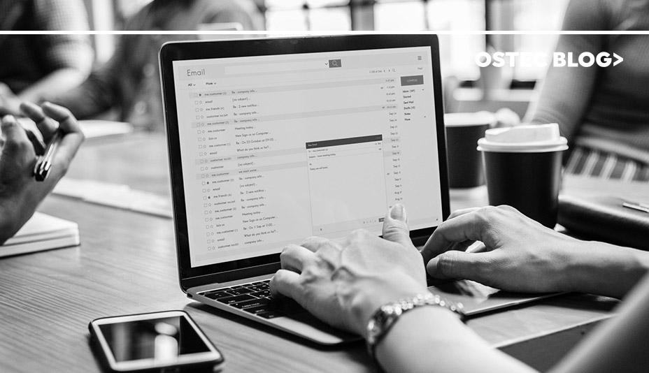 Mulher digitando em notebook que exibe a tela do e-mail. Ao seu lado, sobre a mesa, há um smartphone e um copo de café.
