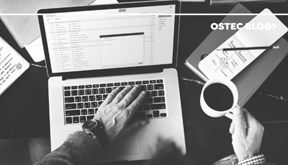 Homem segurando uma xícara de café enquanto confere seus e-mails. Ele corre risco de cair em spear phishing