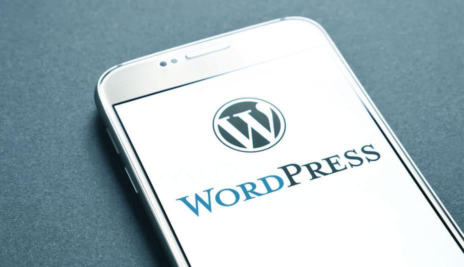 Celular sobre a mesa com a logo do WordPress em uma tela branca onde se pode ler a palavra WordPress.