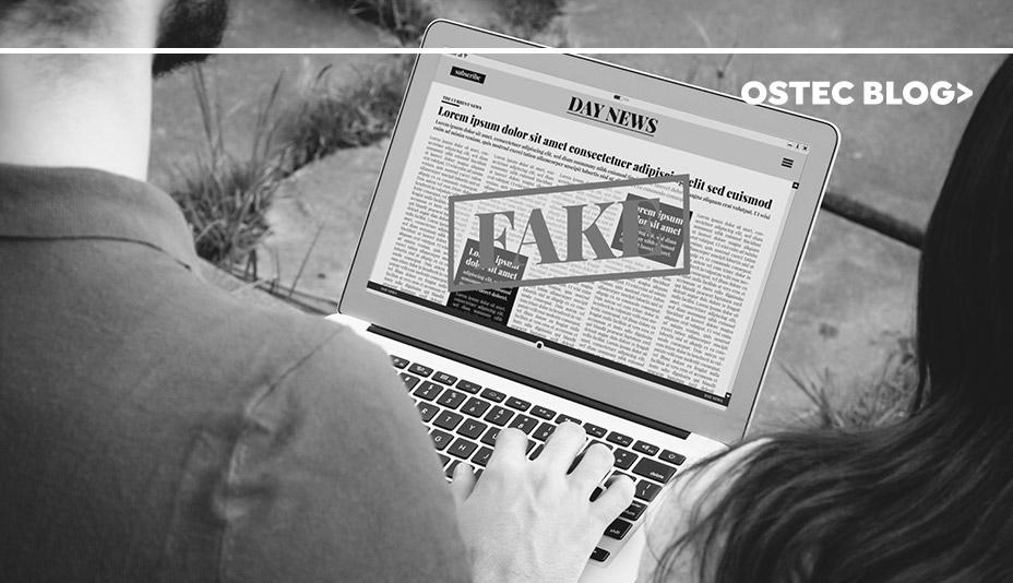 Jovem lendo notícia em seu laptop. É possivel ler a palavra Fake centralizada bem grande no meio da tela.