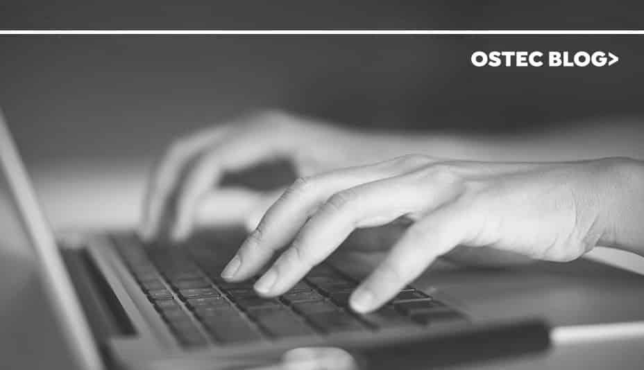 Mãos digitando em teclado de notebook.
