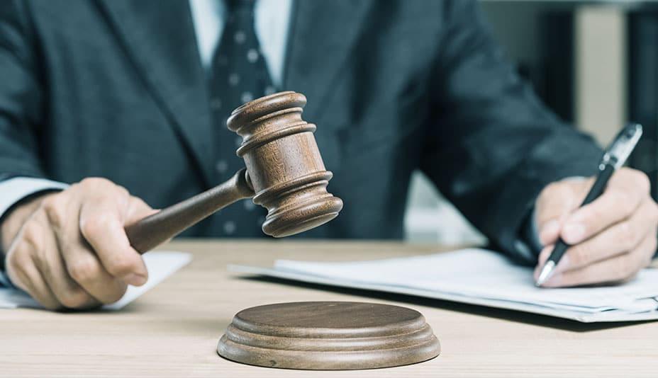 Homem usando terno batendo o martelo de juiz.