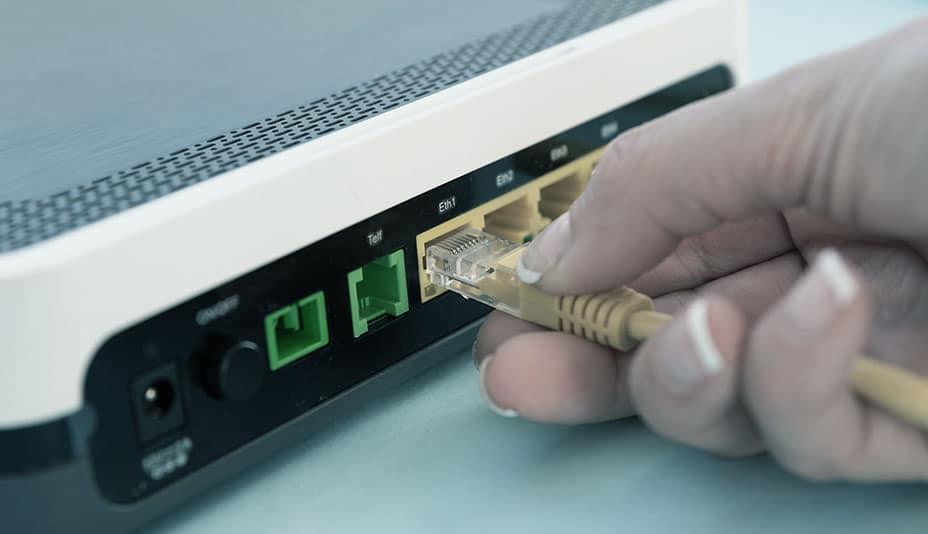 Mão feminina conectando cabo amarelo em modem.