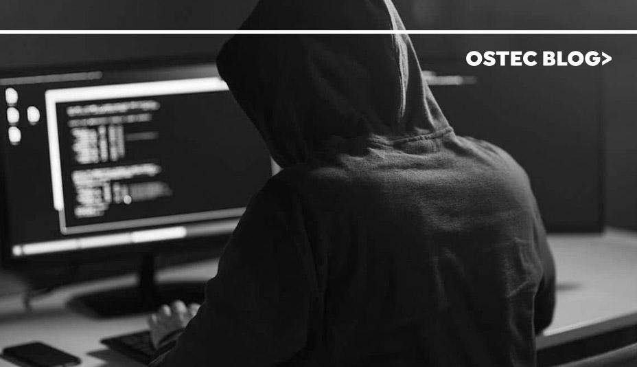 Hacker encapuzado sentado em uma sala escura em frente a um computador