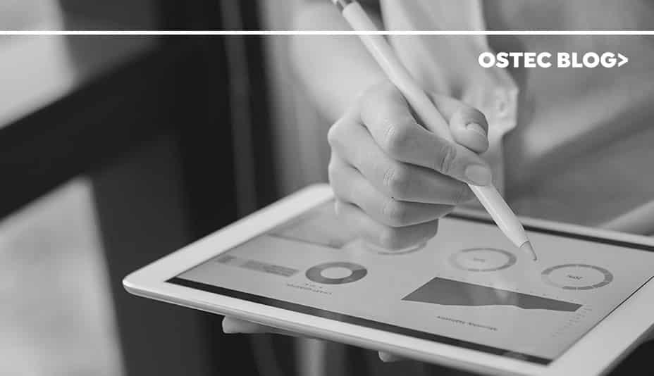 Pessoa segurando um tablet com uma caneta em mãos, simulando a exclusão de dados.