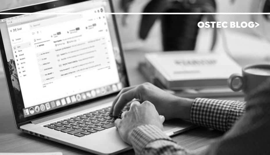 Homem digitando em teclado de laptop, que apresenta a página de e-mail aberta em sua tela.