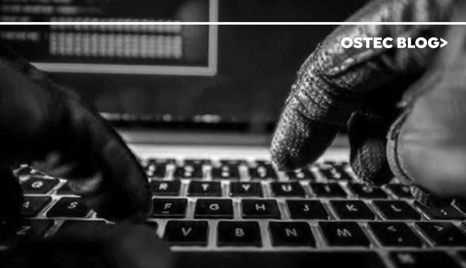 Mãos utilizando luvas de couro digitando em um teclado de notebook.