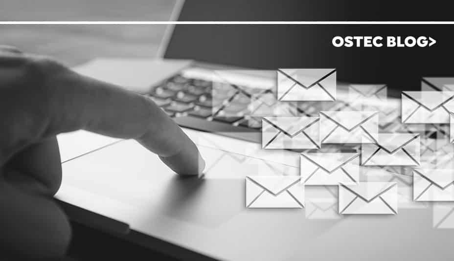 Dedo pressionando o mouse de um notebook com cartinhas vetorizadas simbolizando e-mails sendo enviados.