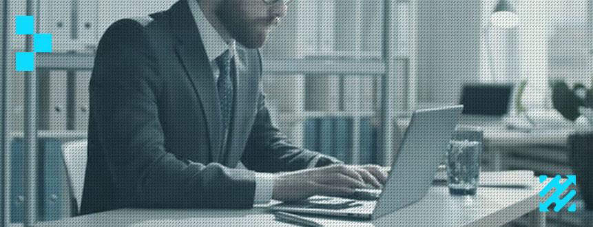 Homem de negócios sentado em sua mesa digitando em um notebook.
