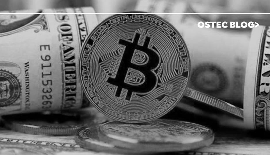 Uma moeda de Bitcoin entre maços de dinheiro.