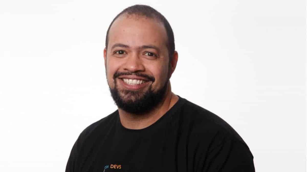 Homem de camiseta preta sorrindo.