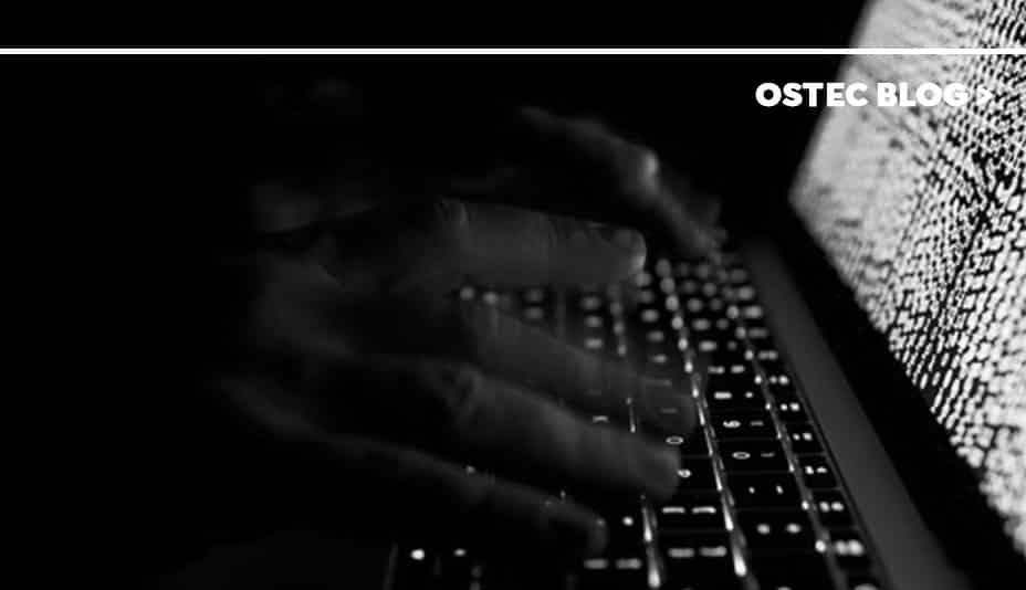 Mãos digitando em teclado de notebook no escuro