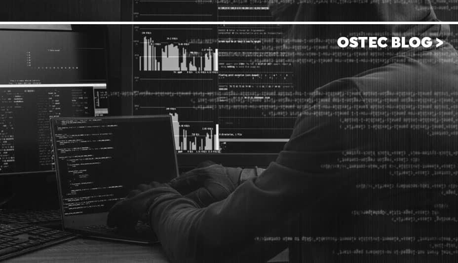 Homem de capuz em frente à telas de computador, digitando em um notebook. Há texto vetorizado sobreposto na imagem.
