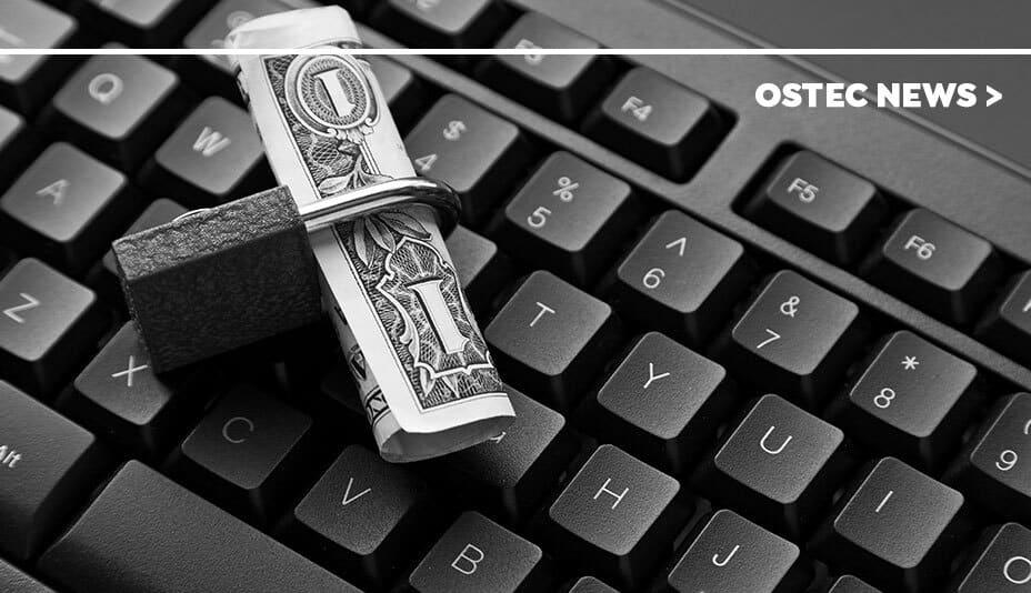 Dinheiro dentro de cadeado que está sobre teclado de computador.