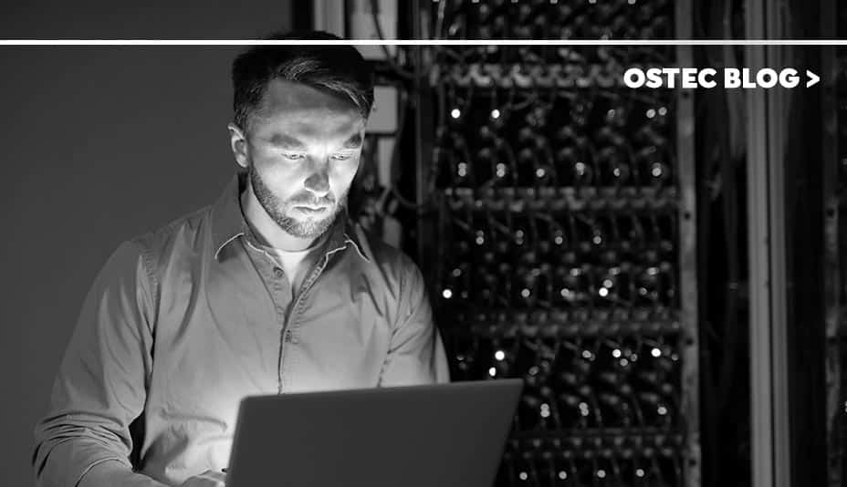 Homem com notebook em data center