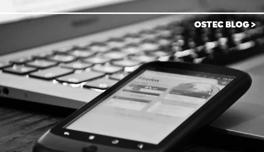 Celular sobre notebook, ambos dispositivos gerenciados por MDM.
