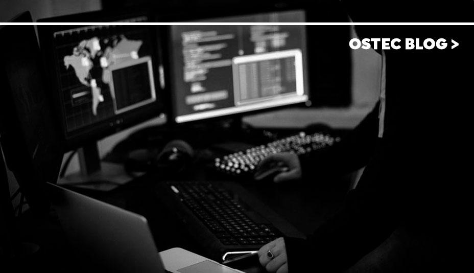 Homem sentado em uma sala escura com três monitores de computador