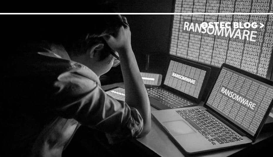Homem em frente a computadores com ransomware em suas telas.