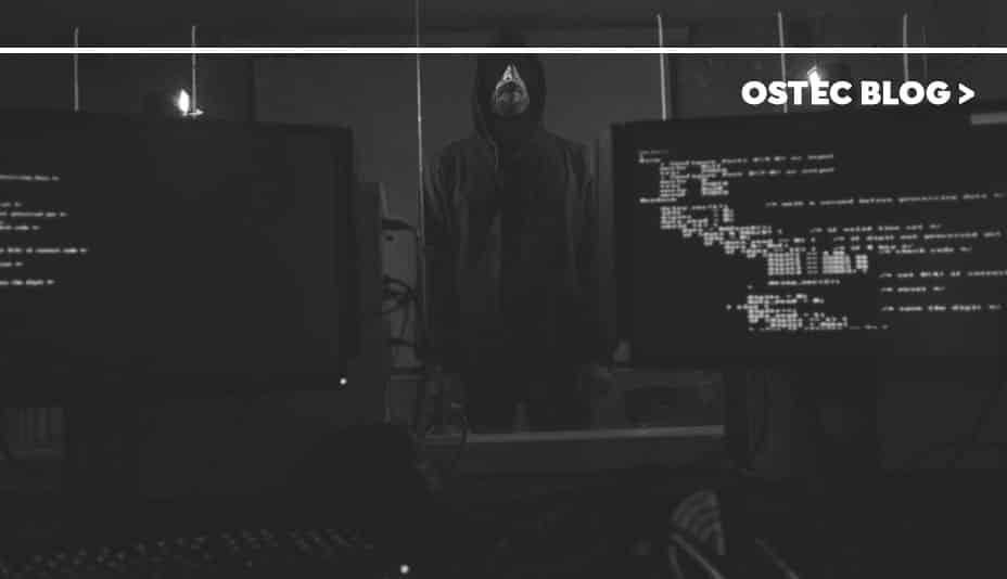 Homem parado entre dois computadores.
