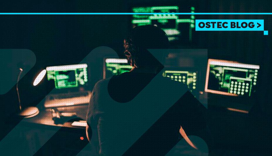 Homem trabalhando com três computadores