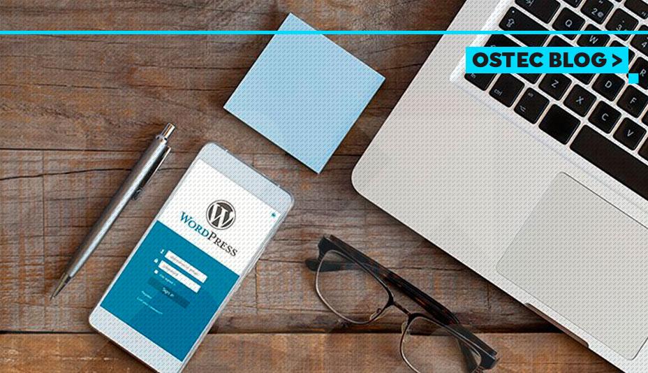 WordPress aberto em celular sobre a mesa, ao lado de notebook e bloco de notas